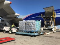 Handlers load pallets of water bound for Puerto Rico into cargo plane chartered by Bennett International Transport for FEMA